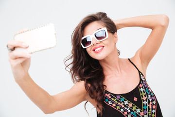 Smiling woman in sunglasses making selfie photo