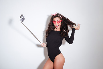 Beautiful woman in bodysuit making selfie photo