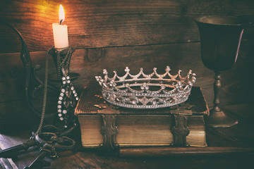 low key image of beautiful diamond queen crown on old book, burning candle. vintage filtered. fantasy middle age concept