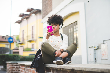 Young handsome afro curly brown hair woman sitting on a brick wall listening music with headphones and smart phone hand hold, looking down tapping the screen - music, happiness, technology concept