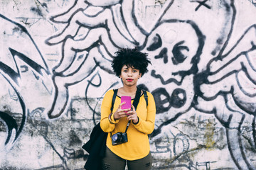 Half length of young handsome african curly brown hair woman leaning on a graffiti wall, holding a smart phone taking a photo - technology, communication, social network concept