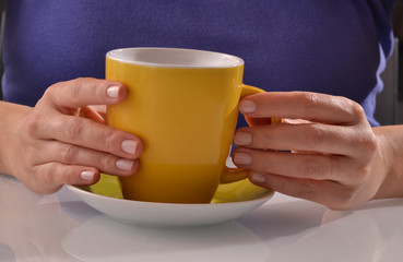 Mujer sujetando una taza de cafe o te caliente.
