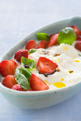 Creamy stracciatella with strawberries, basil, olive oil and balsamic vinegar. Selective focus.