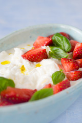 Creamy stracciatella with strawberries, basil and olive oil. Selective focus.
