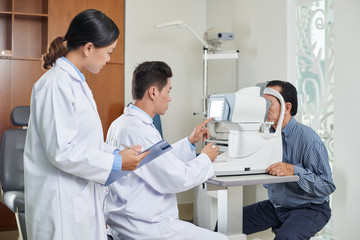 Vietnamese doctor checking eyesight of senior patient