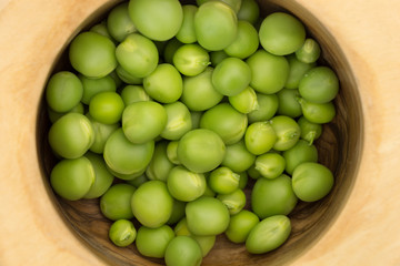 Fresh green peas in wooden bowl closeup background