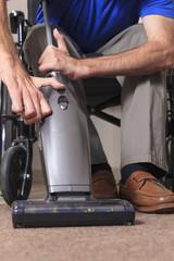 Man in wheelchair vacuuming his house