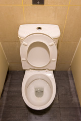 Clean white seat on lavatory toilet in cubical
