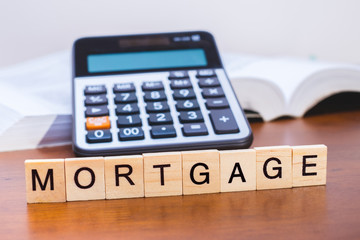 """Calculator with the word """"Mortgage"""" written in wooden block letters"""