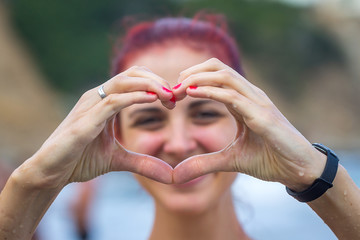 Beautiful Young Lady with her Hands in Heart-Shaped