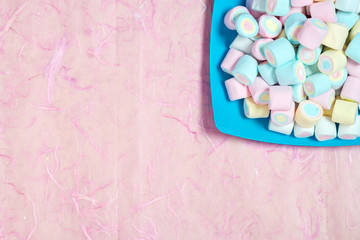 Candy sweet marshmallows in color dish on pink background