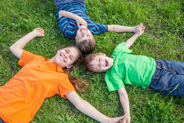 Three kids lying down on green grass