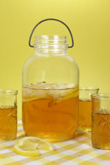 An old fashioned mason jar containing iced tea. Three glasses have tea in as well. A yellow checked table cloth with lemon slices in the foreground.