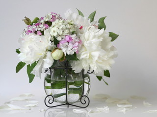 Bouquet of white peony flowers in a vase. Floral decoration with bouquet of peonies and pink carnations flowers in a vase.