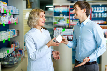Female pharmacist counseling customer about drugs usage