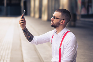 Businessman taking self portrait with iphone. Young hipster man