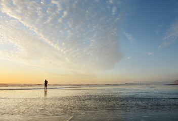 Man walking and taking pictures on the beach at sunrise, Jacksonville, Florida, USA. Beautiful cloudy sky reflected on the beach, pier in the background.