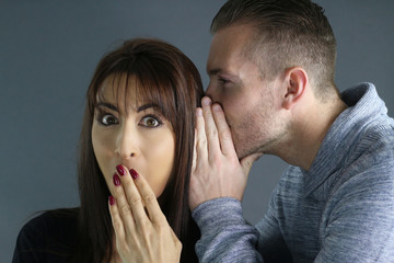 young man telling a secret to a woman