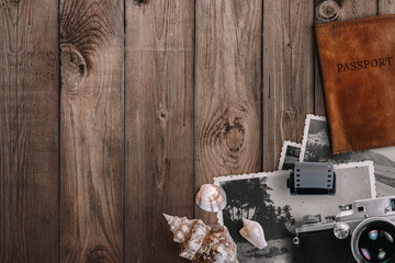 Travel and vacation concept. Items on aged wooden table. Vintage film camera, old photos, film roll, sea shells, passport. Top view with copy space