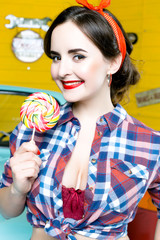 Beauty fashion model girl Eating colourful lollipop. Lollypop. Portrait of Young Woman With Pin Up Hairstyle And Makeup.