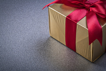 Giftbox in glittery paper on grey background holidays concept