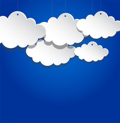 Paper clouds suspended on blue background.