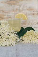 Glass of  elderflower juice and elder-flowers
