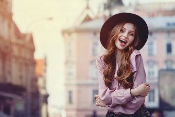 Outdoor portrait of young beautiful fashionable smiling lady posing on a street. Model wearing stylish wide-brimmed hat & clothes. Female fashion. City lifestyle. Toned style instagram filters