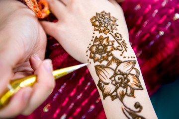 Picture of human hand being decorated with henna tattoo, mehendi