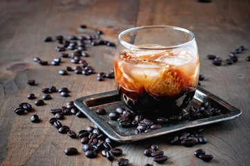 Kahlua liqueur with cream in glasses with coffee beans on a wooden background, selective focus