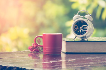 Red coffee cup with alarm clock on wooden table with morning light
