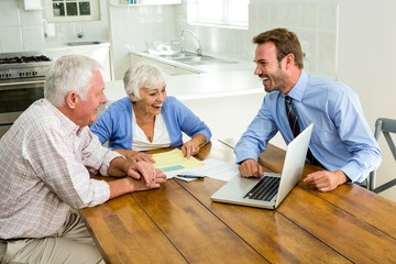 Couple laughing with agent sitting at table