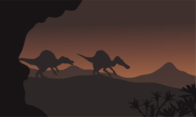 Silhouette of two spinosaurus walking in hills