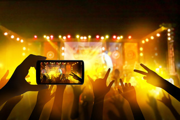 Hand with a smartphone records live music festival, live concert, music festival, happy youth, luxury party, landscape exterior.