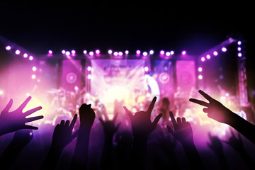 Audience with hands raised at a music festival and lights streaming down from above the stage. live concert, music festival, happy youth, luxury party, landscape exterior.