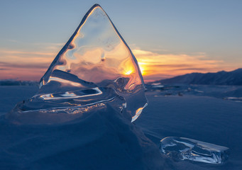 Transparent ice on sunset sky background.