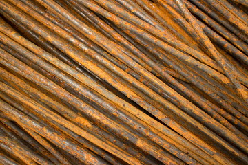 Horizontal CU of thin smooth semi-rusty steel bars stacked in a diagonal position