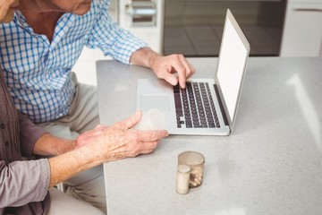 Cropped image of senior couple searching for pills on laptop