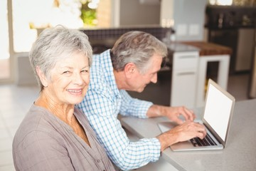 Portrait of senior woman with husband using laptop in background