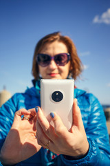 woman taking self-portrait on smartphone