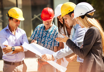 Group of architects and experts discuss about construction.Holding blueprint of new project.