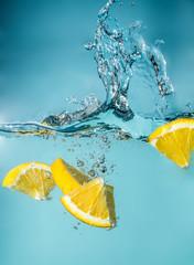 Splash slice orange in water on blue background