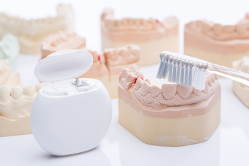 Teeth molds with dental floss and brush on a bright white table