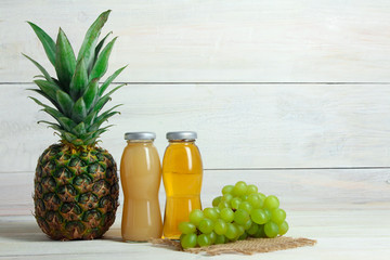 glass bottles with the juice and pineapple with grapes on sackcloth on white wooden background