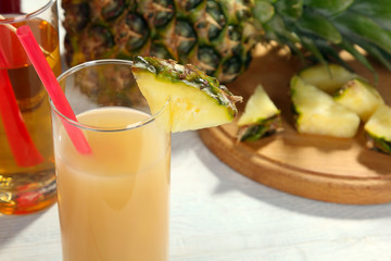 pineapple and apple juice in a glass near a cutting Board with  pineapple  on white wooden table