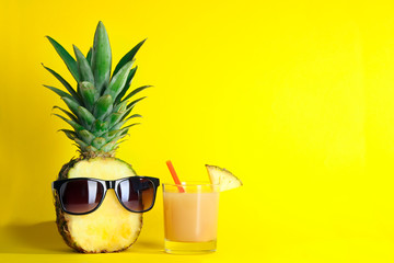 incised pineapple with sunglasses near a glass of juice and a cocktail straw on a yellow background