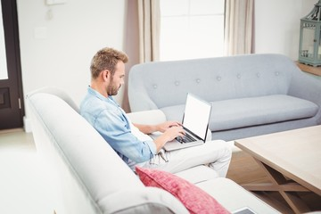 Man using laptop while sitting on sofa in living room