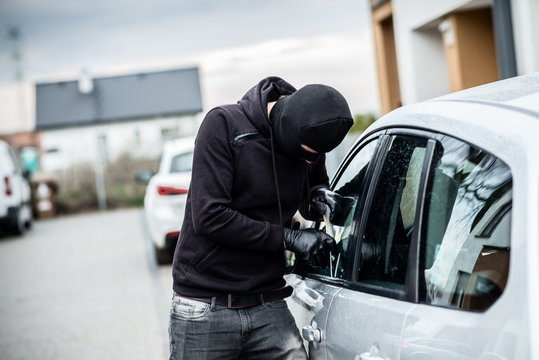 Car thief trying to break into a car with a screwdriver