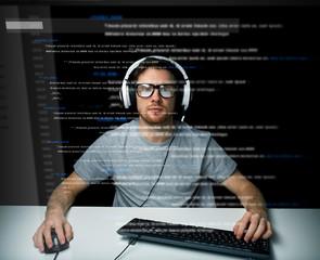 man in headset hacking computer or programming