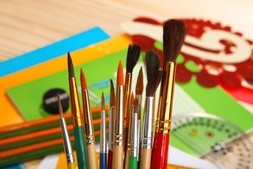 Paint brushes on background of stationery. Selective focus